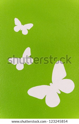 White butterfly painting on green wall