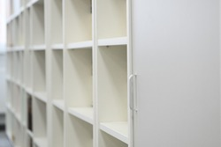 White cabinet with open shelves for storing books, library at school.