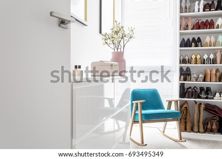White cabinets in elegant classic walk-in closet with open storage for shoes, door, blue vintage armchair and pastel decor #693495349