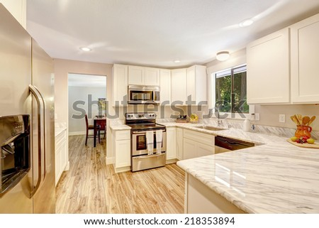 White cabinets with steel appliances and hardwood floor