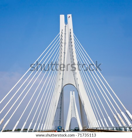 white cable-braced bridge with blue sky background