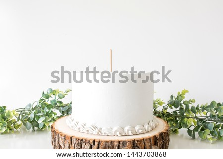 White cake with cake topper stick and blank background space on wood slice and greenery background, cake topper mockup