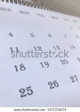 White calendar is black letters which placed on the laptop, can to preparing writing something for planning or organising about work or study schedules on it, window light, minimal concept