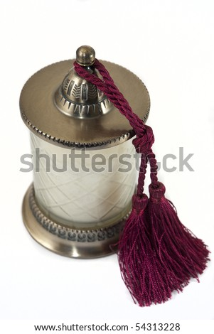 White candle in holder with wine-red tussle hanging on the side - stock photo