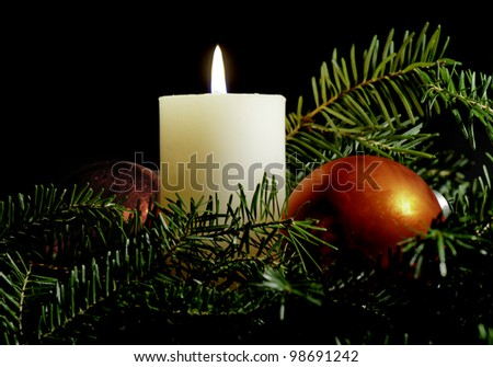 White candle surrounded by red Christmas balls and evergreen branches with black background.