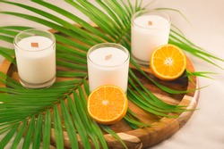 White candles and bright oranges closeup on a wooden tray with palm leaf