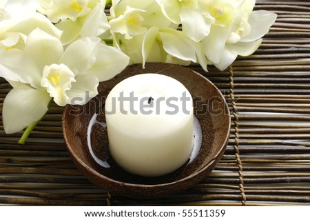 White candles and Orchid on bamboo mat