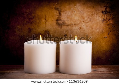White candles burning with a textured vintage background