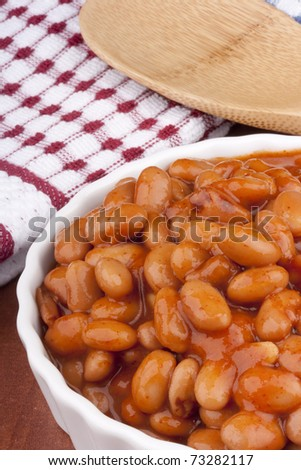 White canned beans in a white ceramic dish with red sauce.