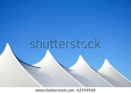 White canvas event tents against blue sky.