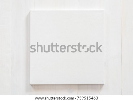 White canvas frame mock up template square size on white wood wall for arts painting and photo hanging interior decoration
