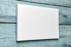 White canvas hanging on light blue wooden wall. Mockup, wall decor, blank canvas stretched on stretcher bar, side view
