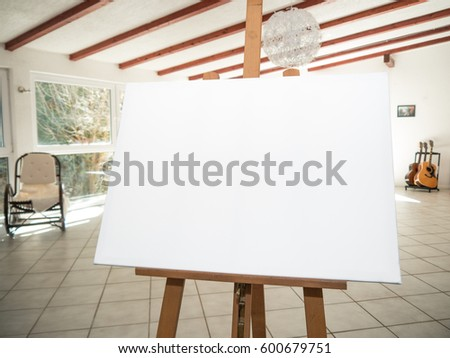 white canvas on a wooden easel in a studio with guitars and a piano