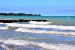 White capped waves along the shores of Lake Michigan with the aqua blue waters all the way out to the horizon.
