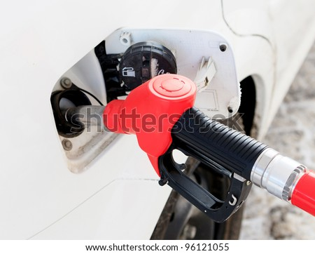 White car at gas station being filled with fuel - stock photo