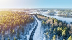 White car drives empty road running along the beautiful blue lake in the cold Finnish winter. Tourists on road trip cruising through the idyllic snow covered countryside and woods.