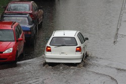 White car is driving through a large puddle in the yard during heavy rain in the city on parked vehicles background, rear top view