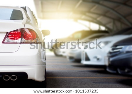White car parking on the road prepare for race or parking. Temporarily blocked in the path, blurry images of cars parked in the sun roof.