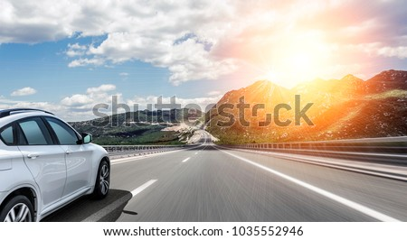 White car rushing along a high-speed highway in the sun.
