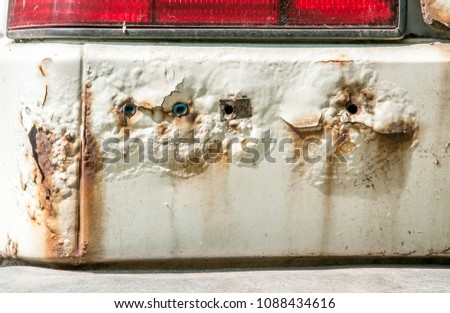 Stock Photo White car with rusty and corroded metal  peeled paint and holes close up