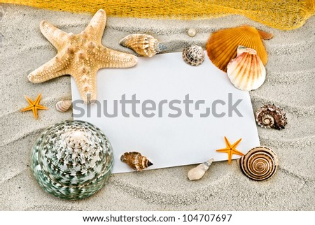White card and few seashells on a sand.