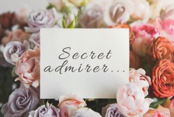 white card for a bouquet with the inscription secret admirer in a bright beautiful bouquet of flowers roses