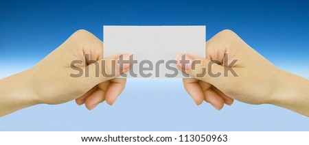 White card in a hand against the blue background