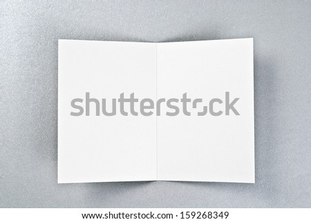 White card or sheet of paper over silver background #159268349