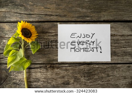 White card with an Enjoy every moment message lying next to a beautiful blooming sunflower on a textured wooden desk in order to encourage you to seize the moment and live a fulfilled life.