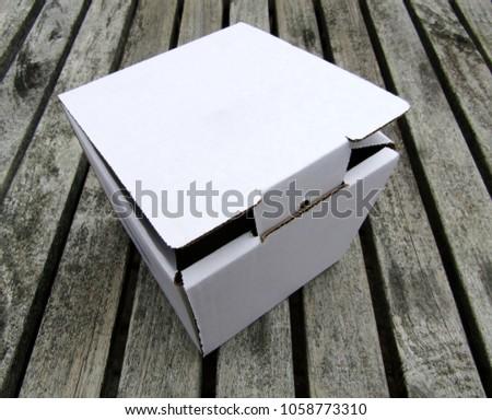 White cardboard mailing box on wooden deck floor