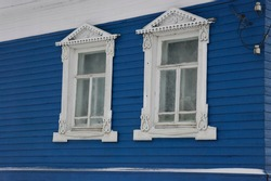 white carved architraves on the Windows of a blue wooden house