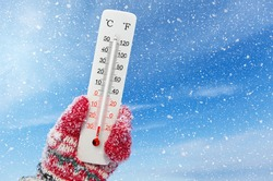 White celsius and fahrenheit scale thermometer in hand. Ambient temperature minus 27 degrees celsius