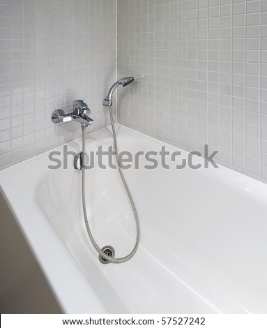 white ceramic bath tub with shower attachment and mozaic tiles