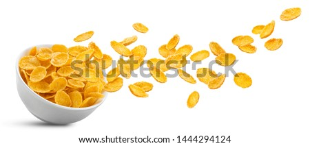 White ceramic bowl of dry uncooked corn flakes. Traditional breakfast yellow cereal in isolated porcelain plate. Falling cornflakes on white background