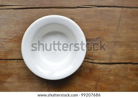 white ceramic bowl on the vintage wooden table