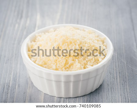 White ceramic bowl with freshly grated parmesan cheese on gray wooden background. Shredded parmesan on grey wooden table.