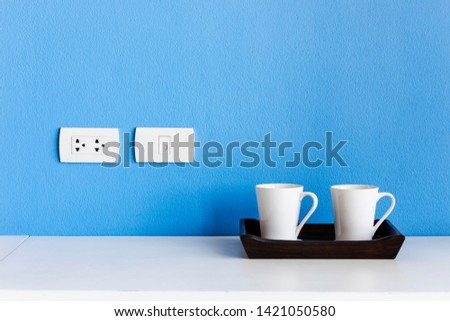 White ceramic coffee cup placed on the table, blue background #1421050580