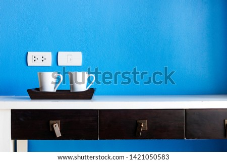 White ceramic coffee cup placed on the table, blue background #1421050583
