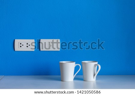White ceramic coffee cup placed on the table, blue background #1421050586