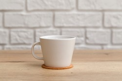 White ceramic cup for coffee on cork coaster on wooden table isolated on white