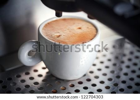 White ceramic cup of fresh espresso with foam in the coffee machine.