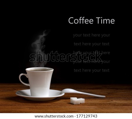 white ceramic cup with hot coffee  on saucer, ceramic spoon and lumps sugar on wooden table on dark background