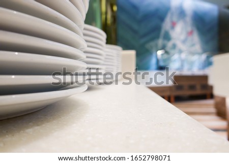 White ceramic dish plate stack row on clean desk table and natural interior design wallpaper art background in organic vegetarian vegan fresh salad catering bistro bar for serve healthy food dining