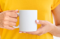 White ceramic mug mockup. Woman wears yellow t-shirt Holding a Warm Cup of Coffee. Copy space for your logo