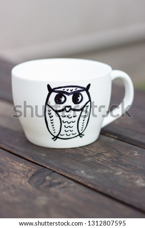 White ceramic mug with permanent marker drawing on wooden table diy handmade cup gift with owl picture