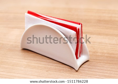 White ceramic napkin holder with paper napkins on a wooden table