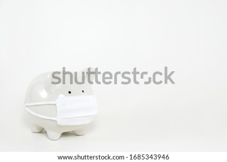 White ceramic piggy bank wearing surgical mask on white background with copy space. Concept for money saving plan, healthcare insurance, coronavirus economic crisis, or financial accounting