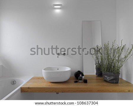 white ceramic washbasin on the wooden surface in a modern bathroom
