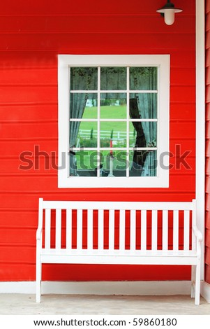 White chair against white window and red wall