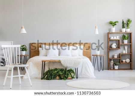White chair near bed with wooden headboard in bright bedroom interior with plants. Real photo #1130736503